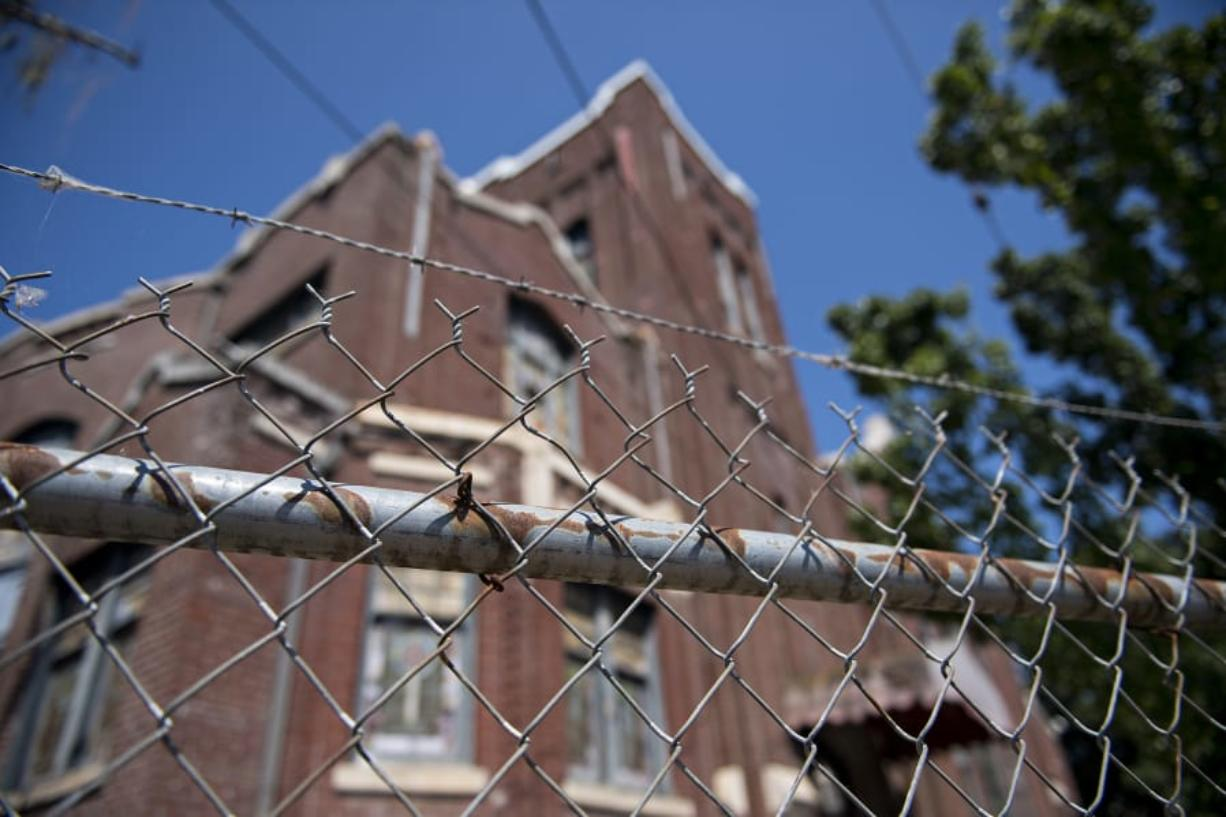 A fence surrounds the old church at 400 W. Evergreen Blvd., where loose bricks could pose a hazard to pedestrians.