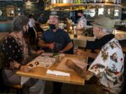 Bartender Derek Devlin, center, takes an order from Marliese Franklin and Jerry Ames during a soft-opening lunch at the second location of Amaro's Table in Hazel Dell. The restaurant's official opening is scheduled for Monday.