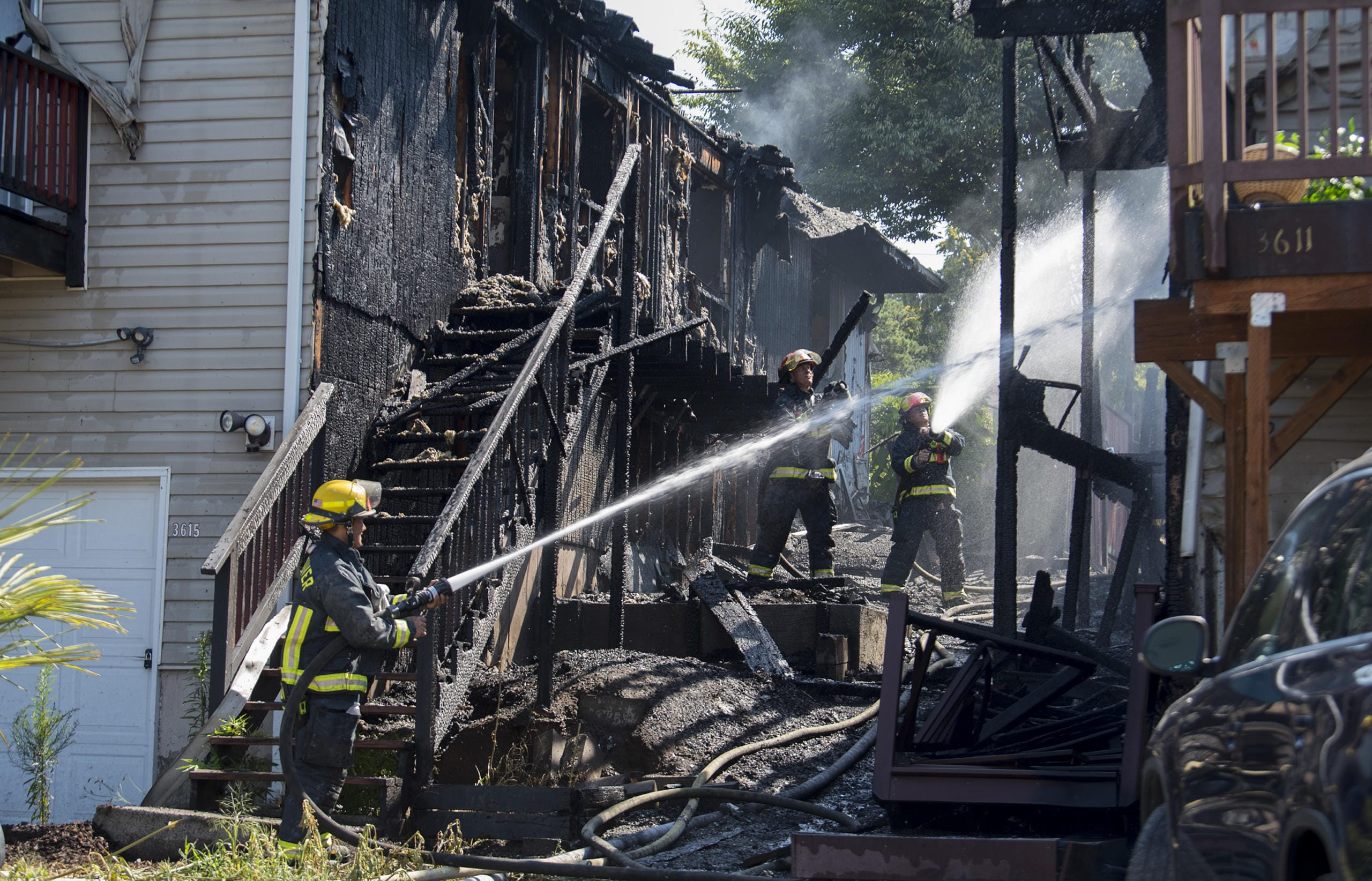 Firefighters work together to extinguish a fire that ripped through two adjoining duplexes on Olive Street on Friday morning, July 31, 2020. (Amanda Cowan/The Columbian)
