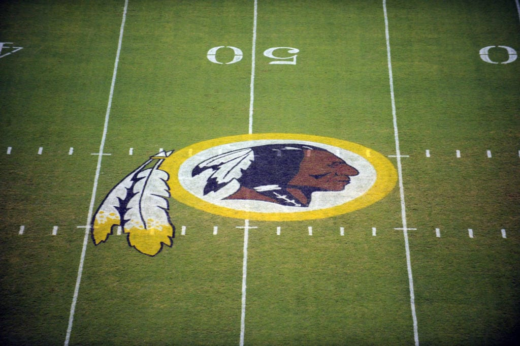 "The Washington Redskins logo is shown on the FedEx Field grass in Landover, Md. The Washington Redskins are undergoing what the team calls a ""thorough review"" of the nickname."