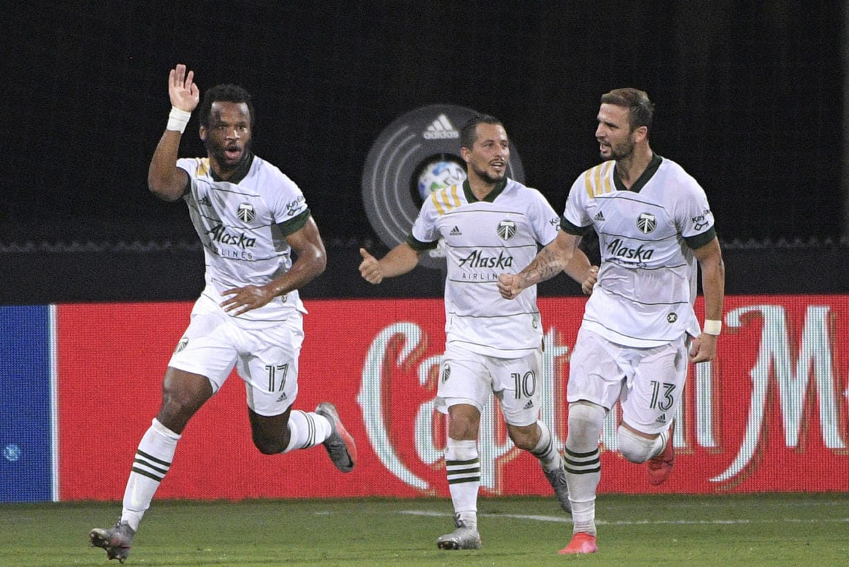 Portland Timbers forward Jeremy Ebobisse (17) celebrates after scoring a goal as midfielder Sebastian Blanco (10) and defender Dario Zuparic (13) come to congratulate him during the second half of an MLS soccer match against the Los Angeles FC, early Friday, July 24, 2020, in Kissimmee, Fla. (AP Photo/Phelan M.