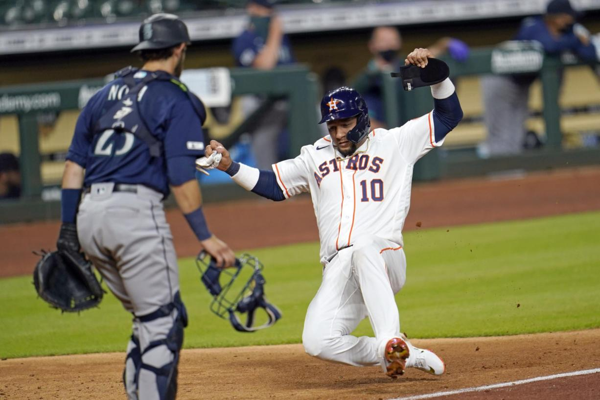 Houston Astros' Yuli Gurriel (10) scores as Seattle Mariners catcher Austin Nola looks on during the seventh inning of a baseball game Friday, July 24, 2020, in Houston. (AP Photo/David J.