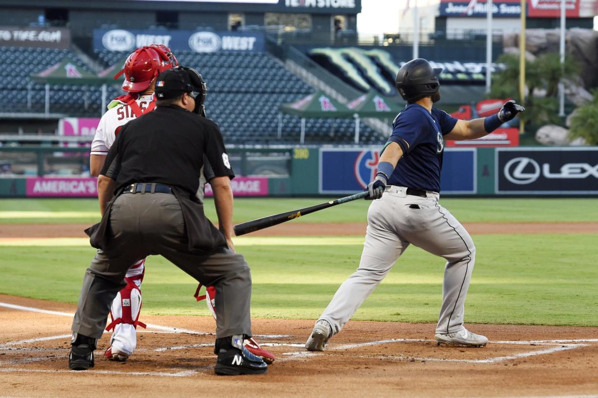 Seattle Mariners' Jose Marmolejos, right, hits a three-run home run as Los Angeles Angels catcher Max Stassi, left, watches along with home plate umpire Doug Eddings during the first inning of a baseball game Thursday, July 30, 2020, in Anaheim, Calif. (AP Photo/Mark J.