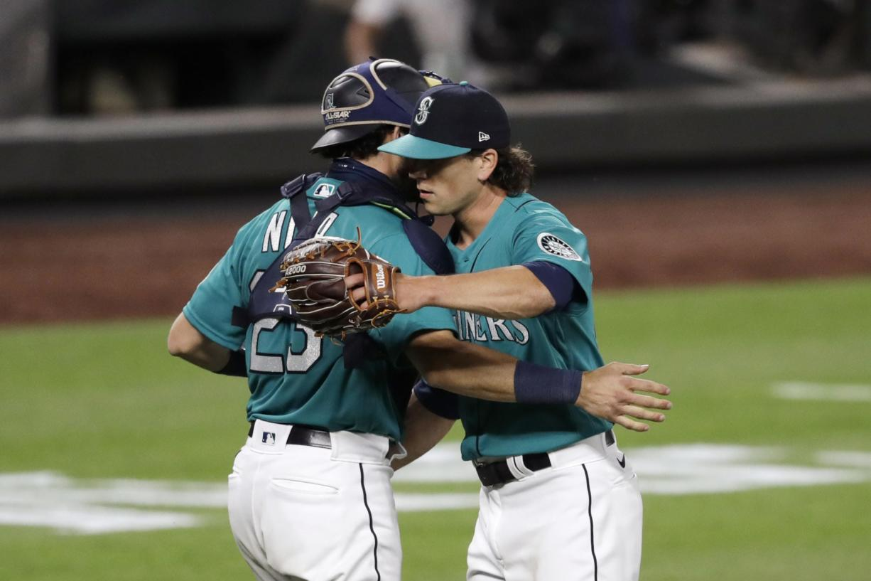 Seattle Mariners closing pitcher Taylor Williams, right, embraces catcher Austin Nola after the team beat the Oakland Athletics in a baseball game during the Mariners home opener Friday, July 31, 2020, in Seattle.