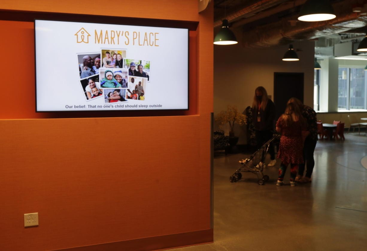 A June 17 video display shows photos and the logo for Mary's Place, a family homeless shelter located inside an Amazon corporate building on the tech giant's Seattle campus.
