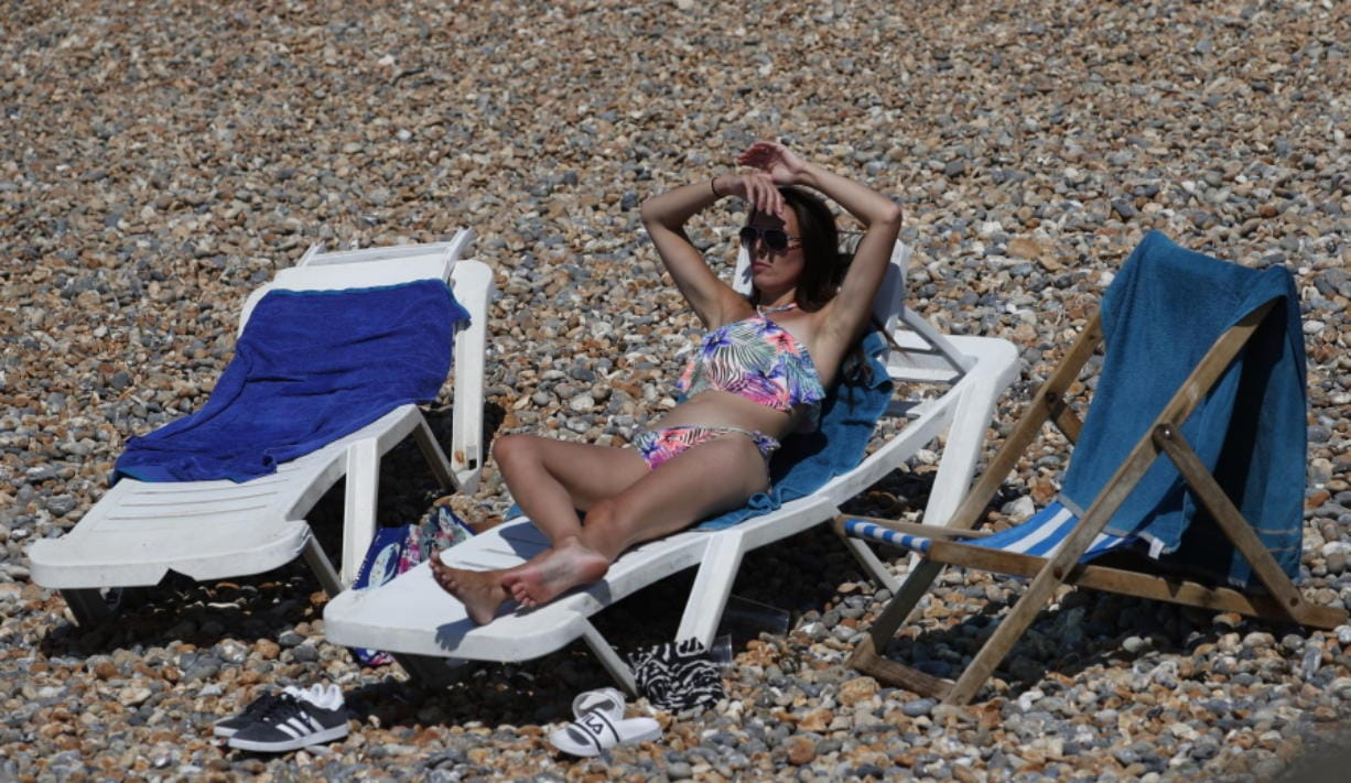 A Beachgoer enjoy the sunshine and sea on what is now Britain's hottest day of the year so far, in Brighton, England, Friday, July 31, 2020. Temperatures have reached 35C (95F) at London's Heathrow Airport.