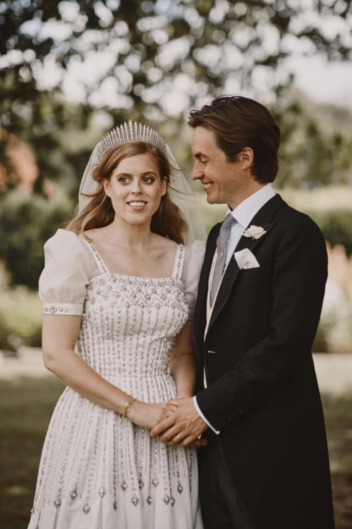 In this photograph released by the Royal Communications of Princess Beatrice and Edoardo Mapelli Mozzi on Sunday, July 19, 2020, Britain's Princess Beatrice and Edoardo Mapelli Mozzi pose for a photo after their wedding at The Royal Chapel of All Saints at Royal Lodge, Windsor, England. The queen'Aos granddaughter and the property tycoon were married on Friday in the Royal Chapel of All Saints at Royal Lodge, Windsor. The 94-year-old British monarch and her 99-year-old husband Prince Philip attended, along with the parents and siblings of the bride and groom.