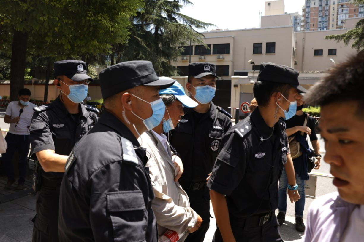 Chinese SWAT police officers escort away a man who tried to show protest slogans on his shirt outside the former United States Consulate in Chengdu in southwest China's Sichuan province on Monday, July 27, 2020. Chinese authorities took control of the former U.S. consulate in the southwestern Chinese city of Chengdu on Monday after it was ordered closed in retaliation for a U.S. order to vacate the Chinese Consulate in Houston.