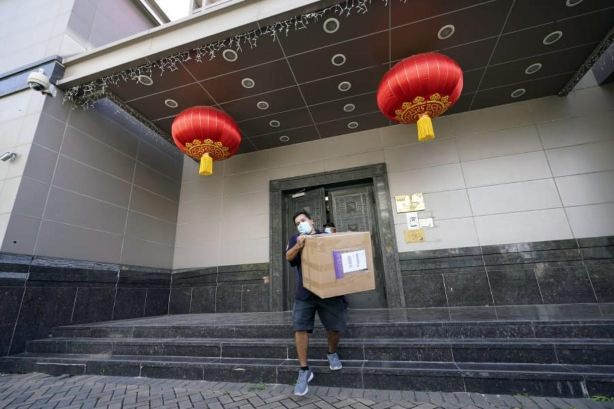 """A FedEx employee removes a box from the Chinese Consulate Thursday, July 23, 2020, in Houston. China says """"malicious slander"""" is behind an order by the U.S. government to close its consulate in Houston,  and maintains that its officials have never operated outside ordinary diplomatic norms.  (AP Photo/David J."""