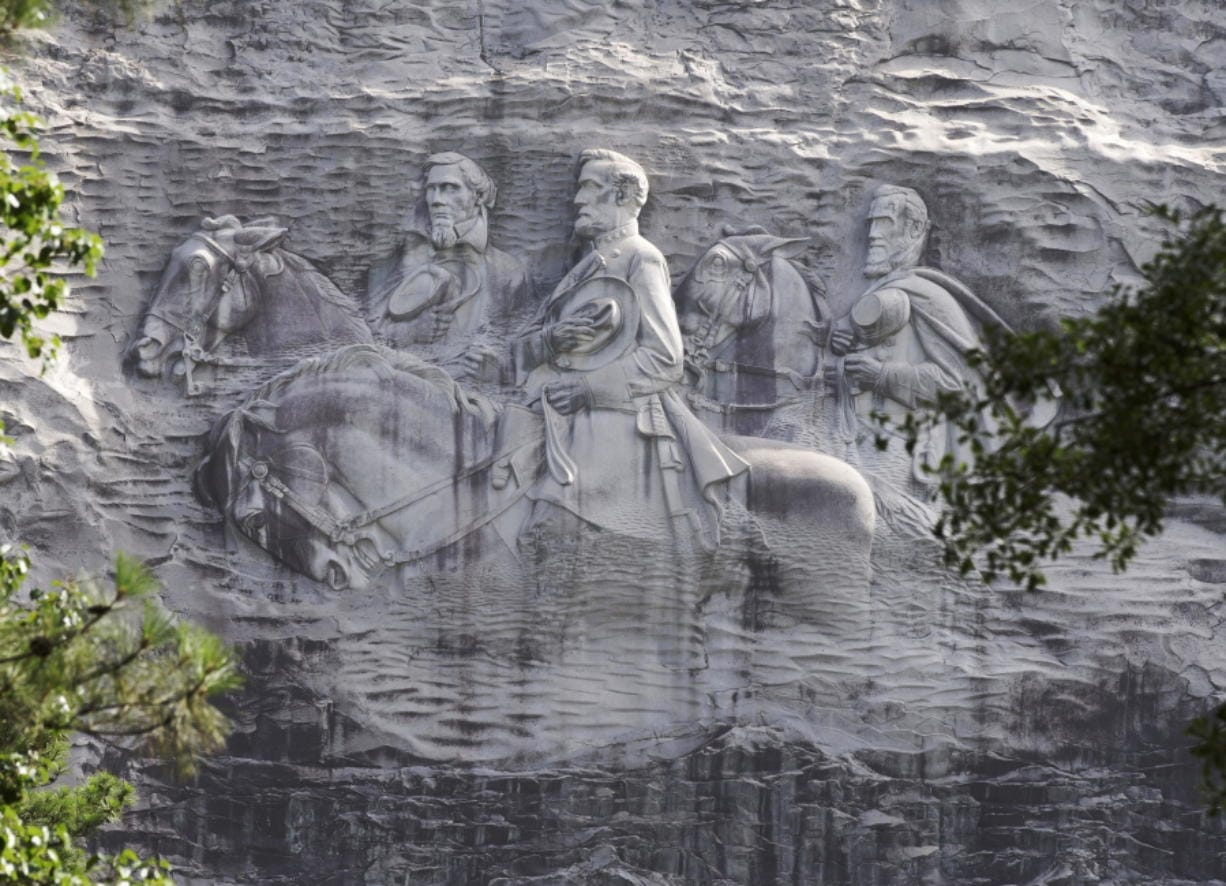 FILE - This June 23, 2015 file photo shows a carving depicting Confederate Civil War figures Stonewall Jackson, Robert E. Lee and Jefferson Davis, in Stone Mountain, Ga. The sculpture is America's largest Confederate memorial.