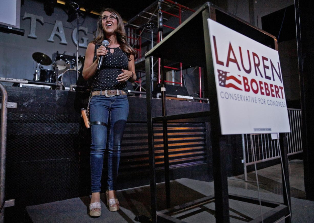 FILE - Businesswoman Lauren Boebert speaks during a watch party at Warehouse 25 Sixty Five in Grand Junction, Colo., after polls closed in Colorado's primary election on Tuesday, June 30, 2020. Boebert, a pistol-packing restaurant owner who has expressed support for a far-right conspiracy theory has upset five-term Colorado U.S. Rep. Scott Tipton. Lauren Boebert is an ardent defender of gun rights and border wall supporter. She will run in November's general election against Diane Mitsch Bush, who won the Democratic nomination on Tuesday.