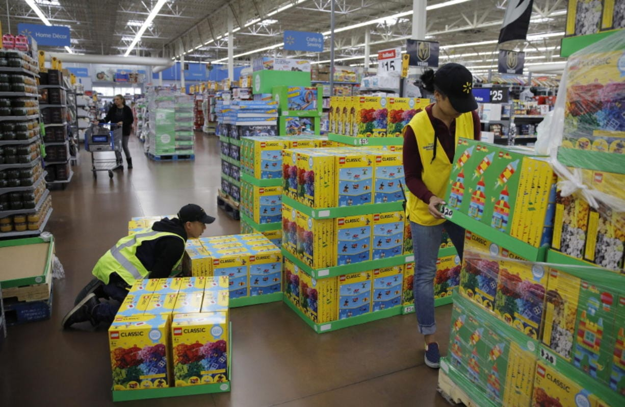 FILE - In this Nov. 27, 2019, file photo Jayln Martin, right, and Dan Villegas stock items in preparation for a holiday sale at a Walmart Supercenter in Las Vegas. On Friday, Jan. 31, 2020, the Labor Department reports on wages and benefits for U.S. workers during the Oct.-Dec. quarter.