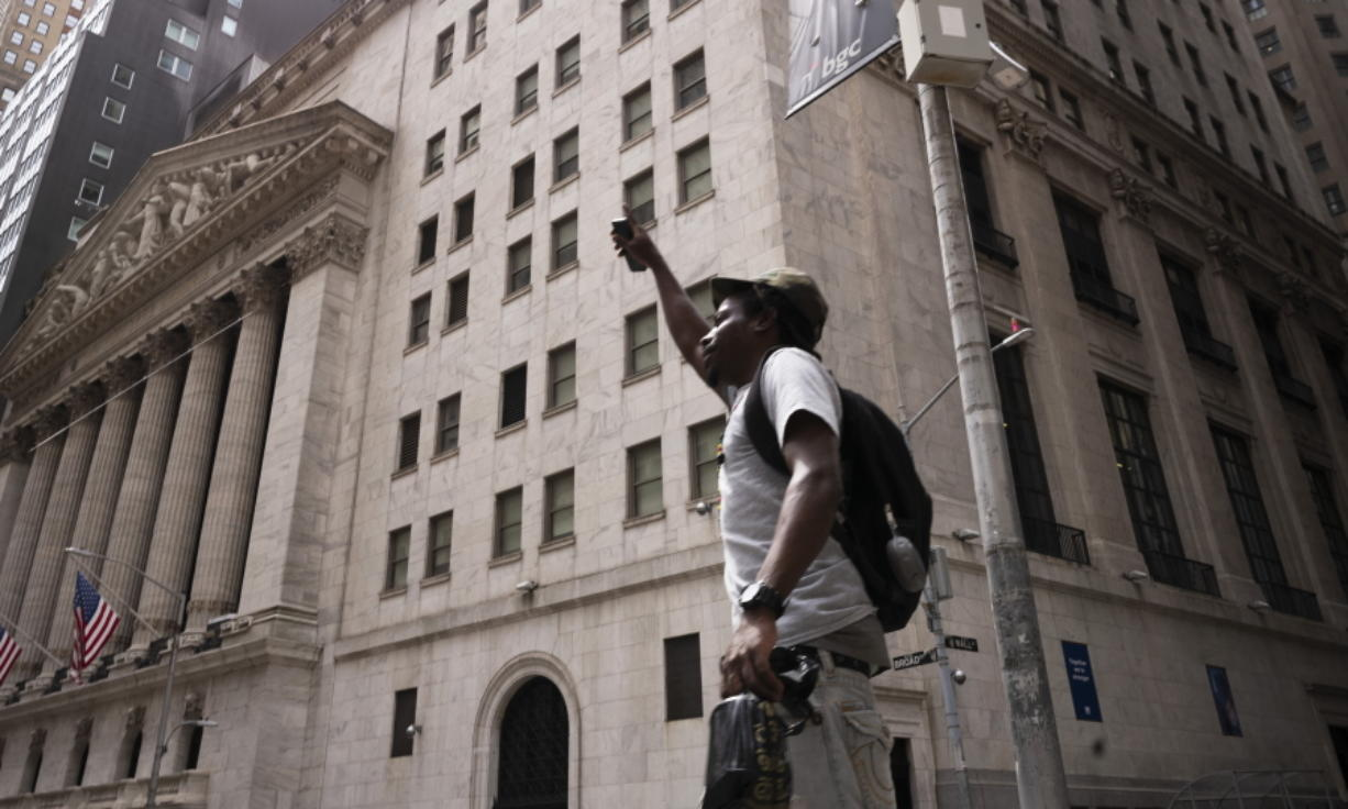 A man lifts his arm as he walks by the New York Stock Exchange, Thursday, July 30, 2020. Stocks are falling on Wall Street Thursday after reports showed that layoffs are continuing at a stubborn pace and that the U.S. economy contracted at a nearly 33% annual rate in the spring.