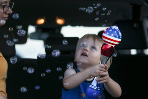 Brittani Scott watches her son, Cooper Scott, 2, play with bubbles while waiting to see a display of fireworks at Nathan Benderson Park, on Friday, July 3, 2020, in Sarasota, Florida.