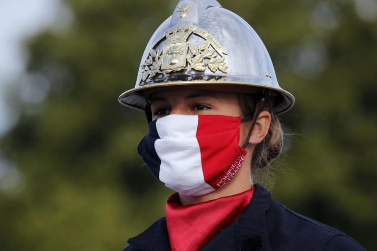 A firefighter wears a face mask with the colors of the French flag, prior to the Bastille Day parade Tuesday, July 14, 2020 on the Champs Elysees avenue in Paris. France are honoring nurses, ambulance drivers, supermarket cashiers and others on its biggest national holiday Tuesday. Bastille Day's usual grandiose military parade in Paris is being redesigned this year to celebrate heroes of the coronavirus pandemic.