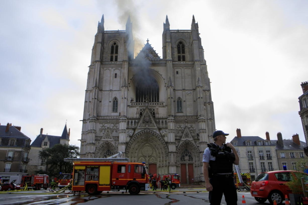Fire fighters brigade work to extinguish the blaze at the Gothic St. Peter and St. Paul Cathedral, in Nantes, western France, Saturday, July 18, 2020. The fire broke, shattering stained glass windows and sending black smoke spewing from between its two towers of the 15th century, which also suffered a serious fire in 1972. The fire is bringing back memories of the devastating blaze in Notre Dame Cathedral in Paris last year that destroyed its roof and collapsed its spire and threatened to topple the medieval monument.