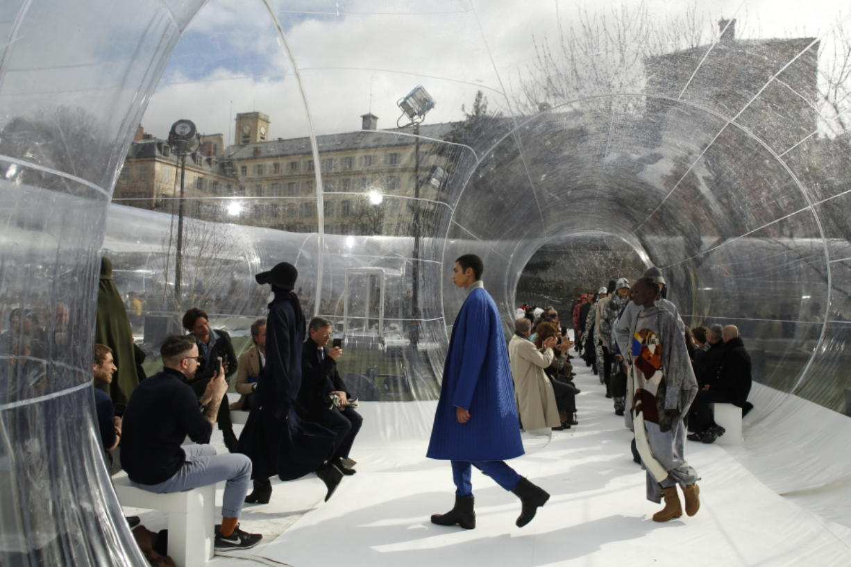 FILE - In this Feb. 26, 2020 file photo, models wear creations for the Kenzo fashion collection during Women's fashion week Fall/Winter 2020/21 presented in Paris. The coronavirus pandemic has instilled extra unpredictability into the already fickle Paris Fashion Week. After first canceling the July shows for menswear and Haute Couture, the French fashion federation has now organized an unprecedented schedule of digital-only events instead.