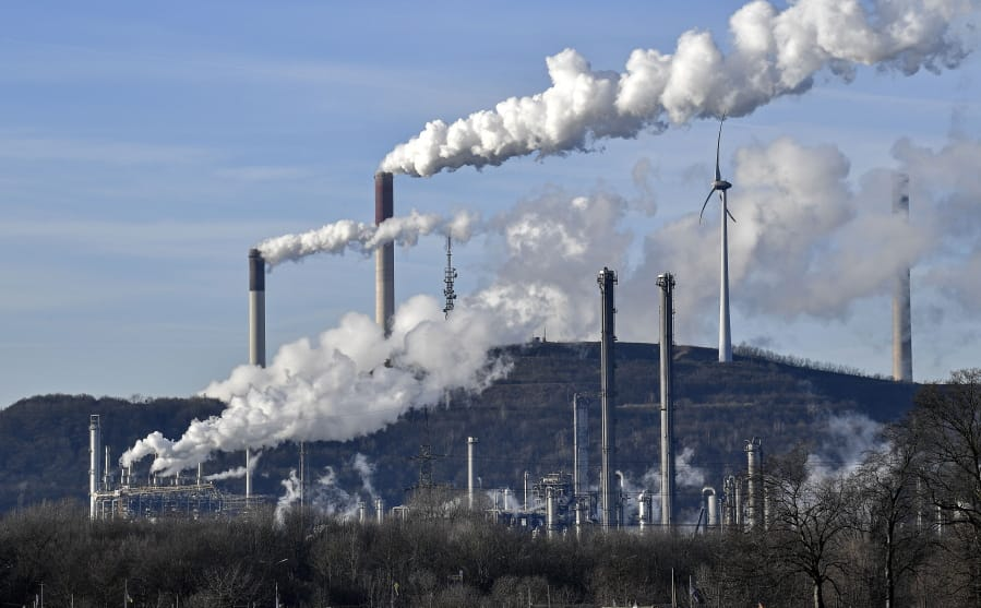 FILE-In this Jan. 16, 2020 file photo an uniper coal-fired power plant and BP refinery steam beside a wind generator in Gelsenkirchen, Germany. The state governors Dietmar Woidke of Brandenburg, Michael Kretschmer of Saxony, Reiner Haseloff of Saxony-Anhalt and Armin Laschet of North Rhine-Westphalia meet in Berlin for the adoption by the Bundestag and Bundesrat of the laws on coal phase-out and structural strengthening in the affected federal states.