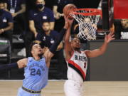 Portland Trail Blazers' CJ McCollum (3)  of the shoots the ball past Memphis Grizzlies' Dillon Brooks  during the first half of an NBA basketball game Friday, July 31, 2020, in Lake Buena Vista, Fla.