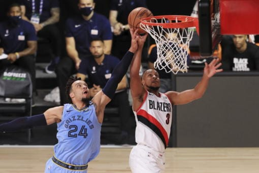 Portland Trail Blazers' CJ McCollum (3)  of the shoots the ball past Memphis Grizzlies' Dillon Brooks  during the first half of an NBA basketball game Friday, July 31, 2020, in Lake Buena Vista, Fla. (Mike Ehrmann/Pool Photo via AP)