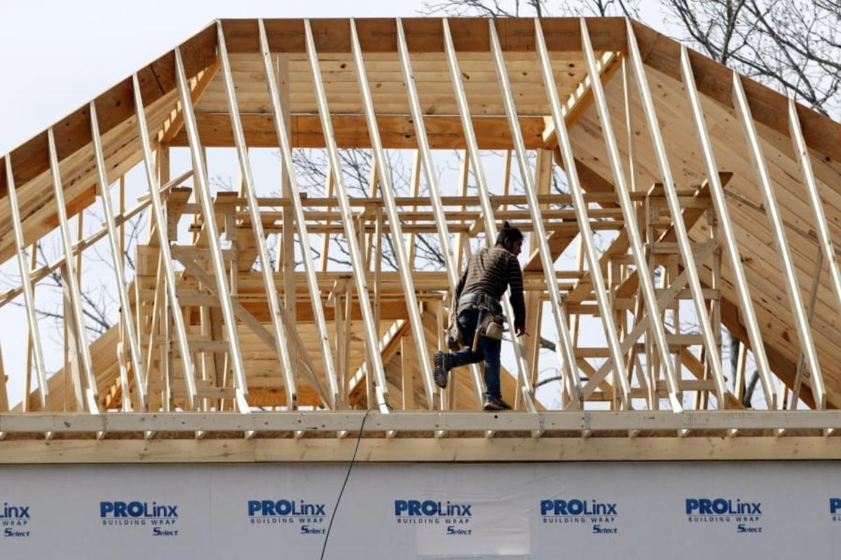In this March 25, 2020, photo, a construction worker walks along a roof on a new home in Nashville, Tenn.  US home construction rebounded 4.3% in May after steep declines caused by shutdowns due to the coronavirus.
