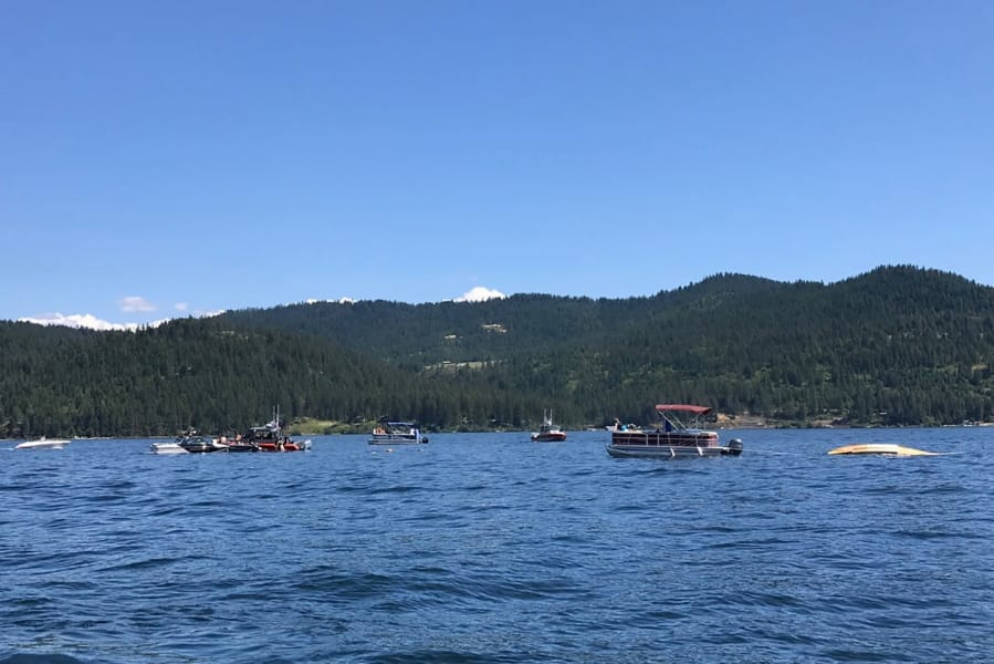 Boaters flag down authorities to a crashed seaplane near Powderhorn Bay on Lake Coeur d'Alene on Sunday, July 5, 2020, south of Coeur d'Alene, Idaho. The downed plane can be seen in the right side of the image. Two people died in a plane crash Sunday over Lake Coeur d'Alene Sunday, the Kootenai County Sheriff's Office told the Spokane Spokesman-Review. Investigators are checking initial reports that there were a total of eight passengers and crew on the two planes, the sheriff's office said in a statement Sunday night.