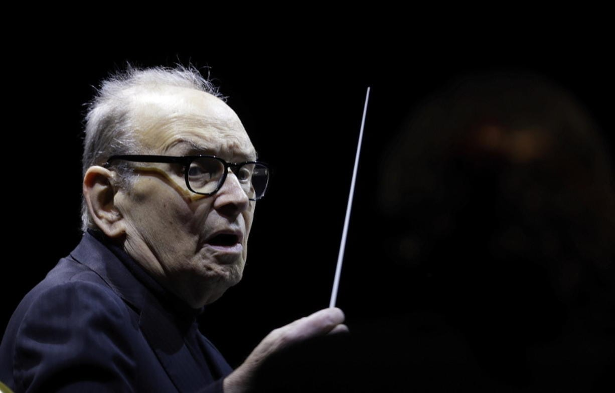 "FILE - In this file photo dated Tuesday, March 6, 2018, Italian composer Ennio Morricone directs an ensemble during a concert of his ""60 Year Of Music World Tour"", in Milan, Italy. Morricone, who created the coyote-howl theme for the iconic Spaghetti Western ""The Good, the Bad and the Ugly"" and the soundtracks such classic Hollywood gangster movies as ""The Untouchables,"" died Monday, July 6, 2020 in a Rome hospital at the age of 91."