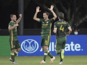 Portland Timbers midfielder Diego Valeri (8) celebrates after scoring a goal as midfielder Sebastian Blanco, left, and defender Jorge Villafana (4) come to congratulate him during the second half of an MLS soccer match against the Houston Dynamo, Saturday, July 18, 2020, in Kissimmee, Fla. (AP Photo/Phelan M.