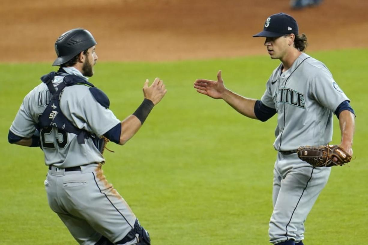 Seattle Mariners relief pitcher Taylor Williams, right, celebrates with catcher Austin Nola after a baseball game against the Houston Astros Sunday, July 26, 2020, in Houston. The Mariners won 7-6. (AP Photo/David J.