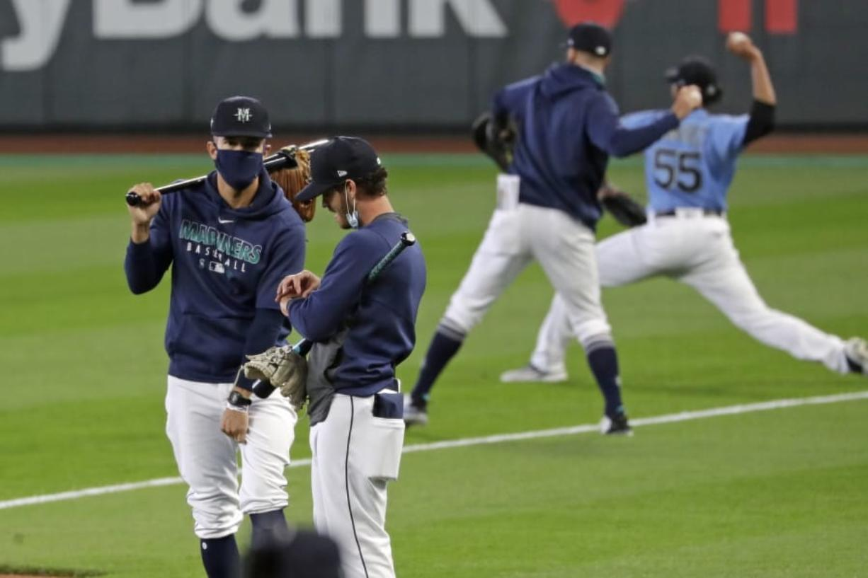 """Seattle Mariners players and coaches begin a """"summer camp"""" baseball workout on their ballpark field Friday, July 3, 2020, in Seattle."""