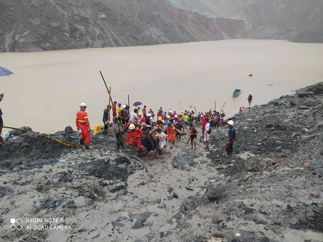 In this photo released from Myanmar Fire Service Department, rescuers carry a recovered body of a victim in a landslide from a jade mining area in Hpakant, Kachin state, northern Myanmar Thursday, July 2, 2020. Myanmar government says a landslide at a jade mine has killed dozens of people.