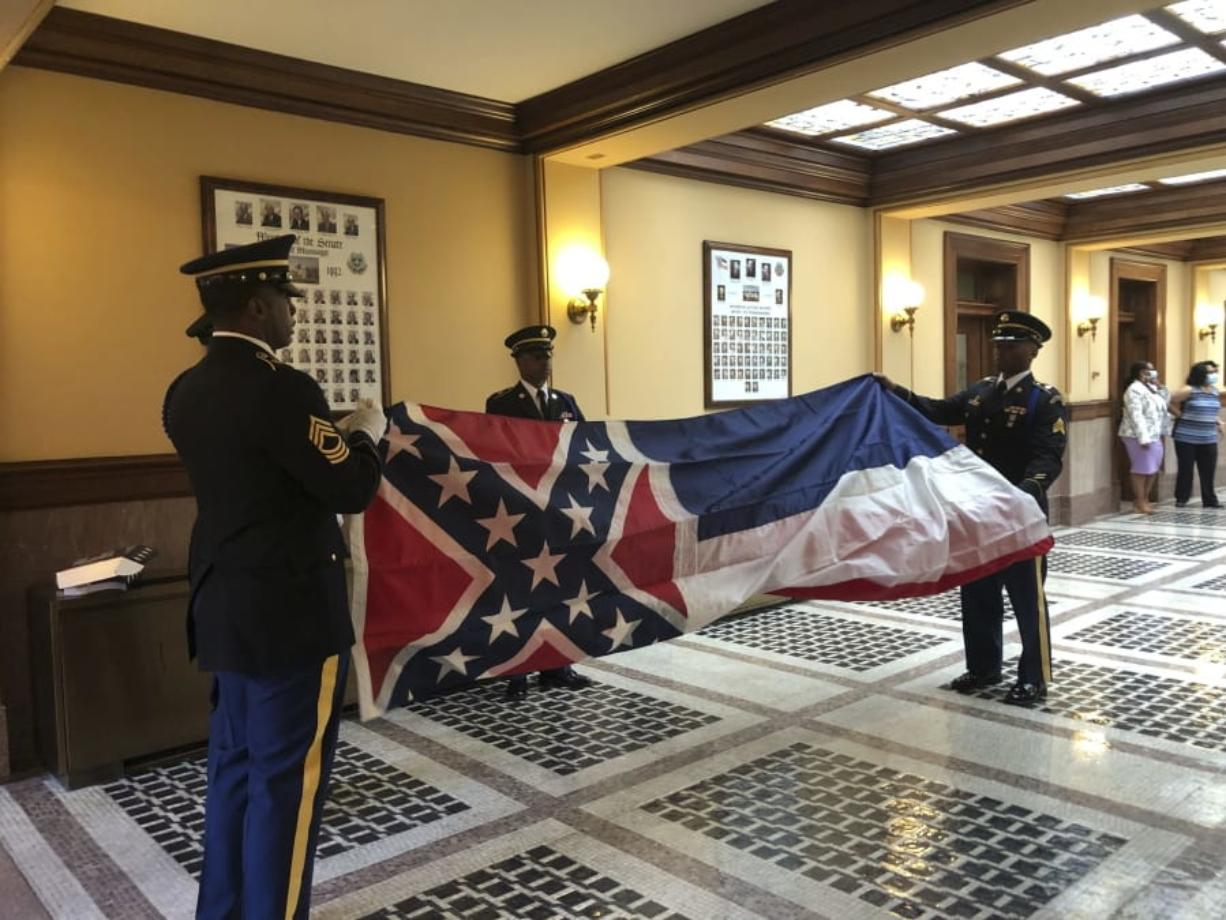 Honor guard members from the Mississippi National Guard practice folding the former Mississippi flag before a ceremony to retire the banner on Wednesday, July 1, 2020, inside the state Capitol in Jackson. The ceremony happened a day after Republican Gov. Tate Reeves signed a law that removed the flag's official status as a state symbol. The 126-year-old banner was the last state flag in the U.S. with the Confederate battle emblem.