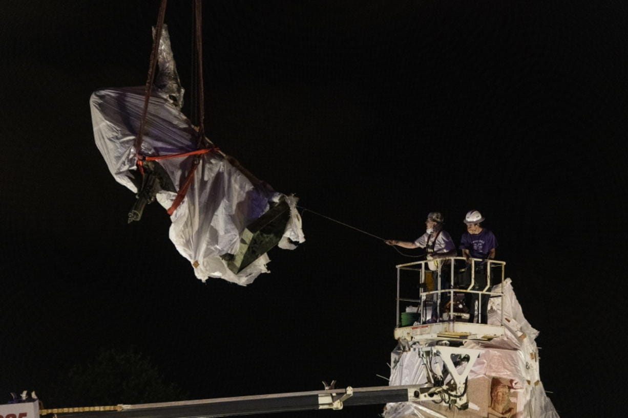 City municipal crews help guide the Christopher Columbus statue in Grant Park as it is removed by a crane, Friday, July 24, 2020, in Chicago. A statue of Christopher Columbus that drew chaotic protests in Chicago was taken down early Friday amid a plan by President Donald Trump to dispatch federal agents to the city.