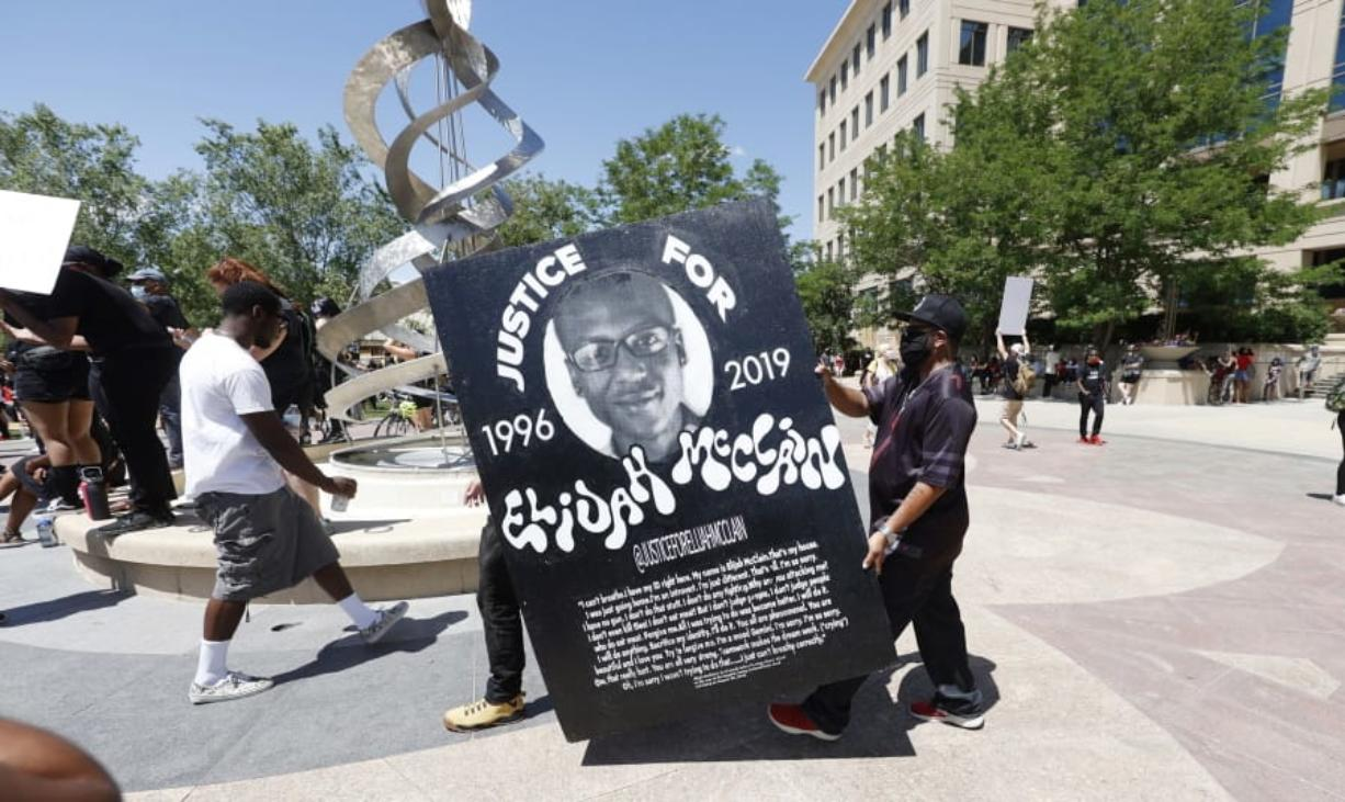 "FILE - In this June 27, 2020, file photo, demonstrators carry a giant placard during a rally and march over the death of 23-year-old Elijah McClain outside the police department in Aurora, Colo. Multiple suburban Denver police officers have been placed on paid administrative leave amid an investigation into photos of them related to the case of a Black man who died last summer after he was stopped and restrained, police said Monday, June 29, 2020. The interim police chief of the city of Aurora, Vanessa Wilson, said in a statement that the suspended officers were ""depicted in photographs near the site where Elijah McClain died."" But her statement did not provide more details about what the images show."