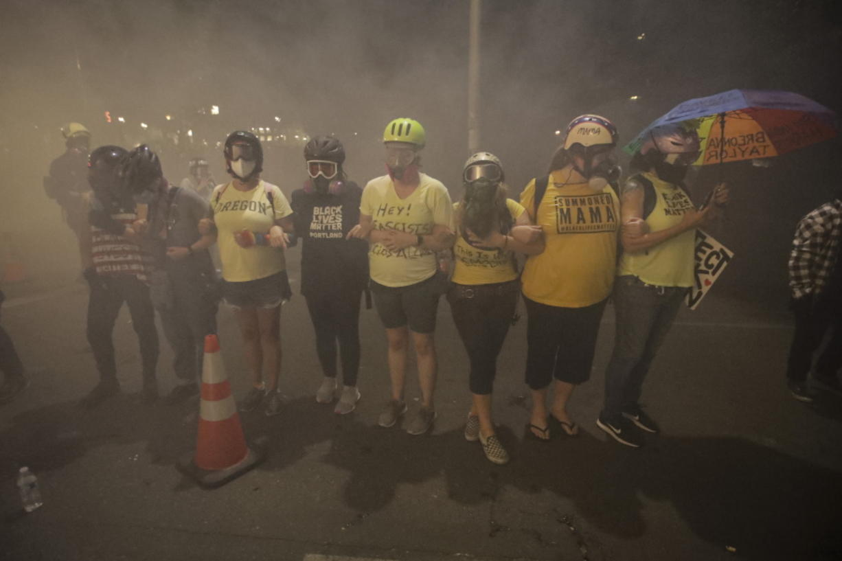 Members of the 'Wall of Moms' protest group lock arms as they are tear-gassed by federal officers during a Black Lives Matter protest at the Mark O. Hatfield United States Courthouse Monday, July 27, 2020, in Portland, Ore.