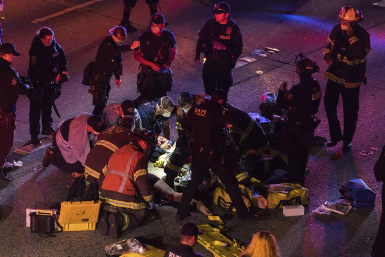 Emergency workers tend to an injured person on the ground after a driver sped through a protest-related closure on the Interstate 5 freeway in Seattle, authorities said early Saturday, July 4, 2020. Dawit Kelete, 27, has been arrested and booked on two counts of vehicular assault.