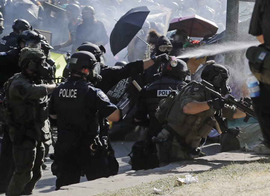Police pepper spray protesters, Saturday, July 25, 2020, near Seattle Central Community College in Seattle. A large group of protesters were marching Saturday in Seattle in support of Black Lives Matter and against police brutality and racial injustice. (AP Photo/Ted S.