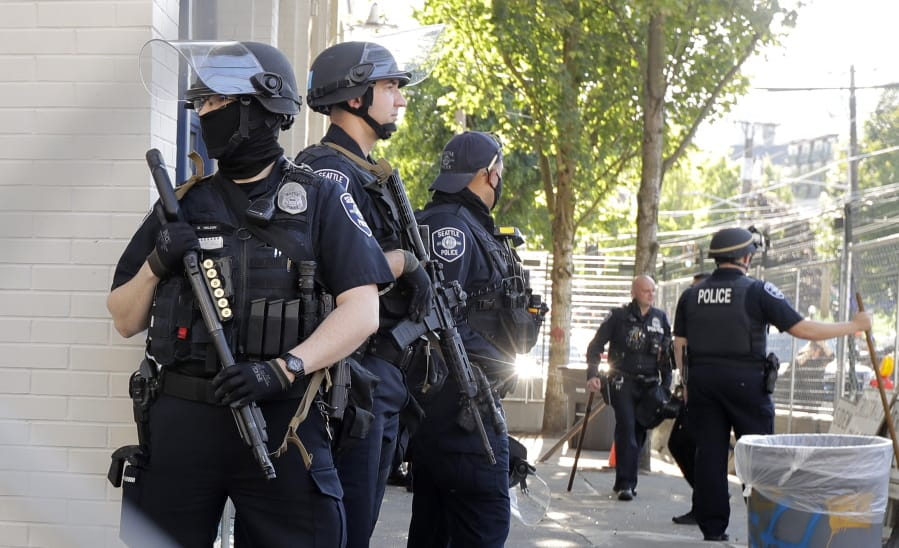 Seattle Police officers hold weapons as they stand guard outside the East Precinct Building, Sunday, July 19, 2020 in Seattle. Protesters broke windows at the building earlier in the afternoon. (AP Photo/Ted S.