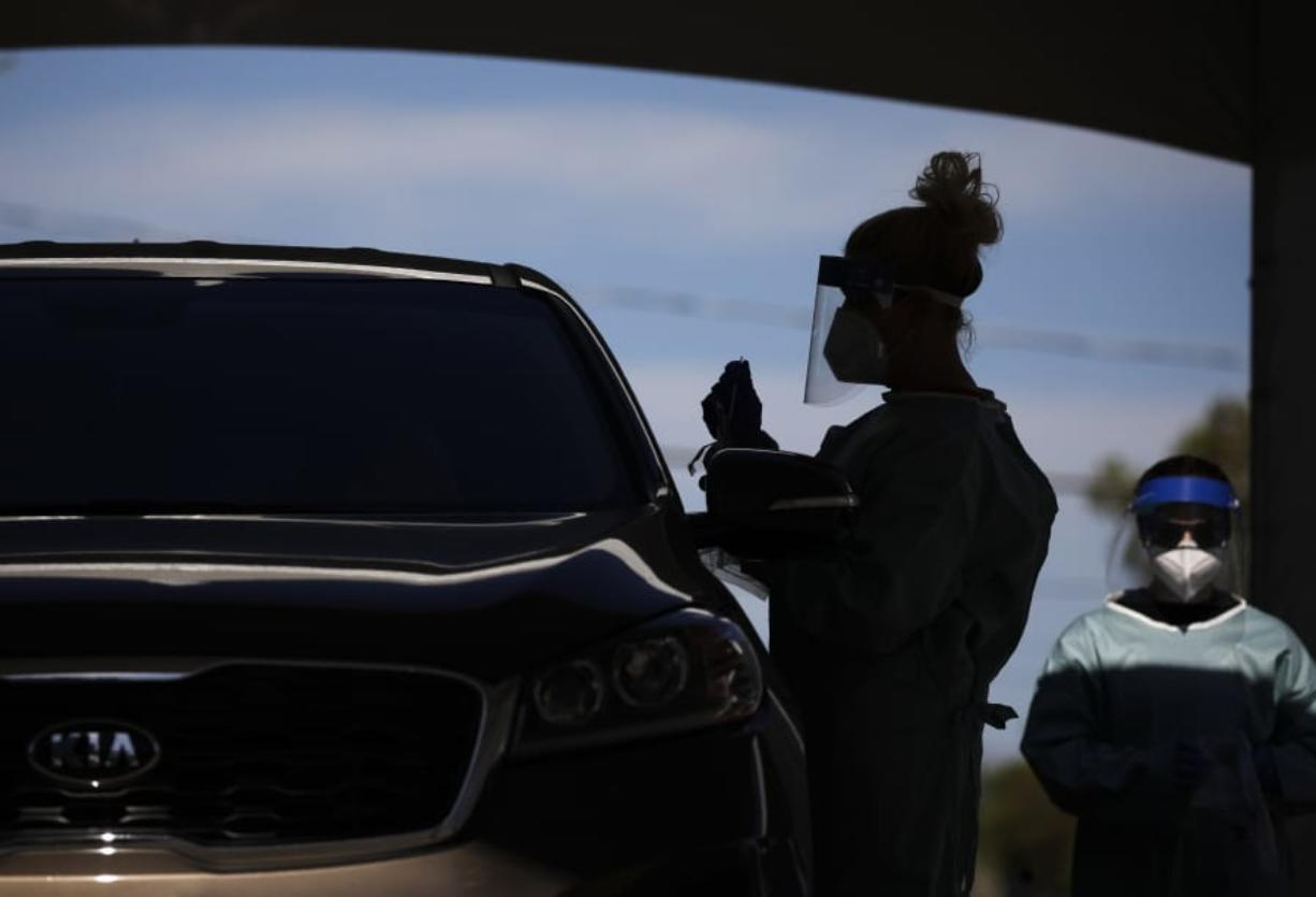 FILE - In this July 10, 2020, file photo healthcare workers test patients in their cars at a drive-thru coronavirus testing site in Las Vegas.