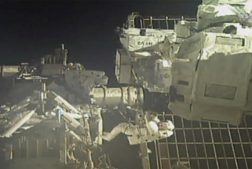In this image taken from NASA video, commander Chris Cassidy, right, and NASA astronaut Bob Behnken perform their second spacewalk in under a week Wednesday, July 1, 2020, to replace old batteries outside the International Space Station. (NASA via AP)