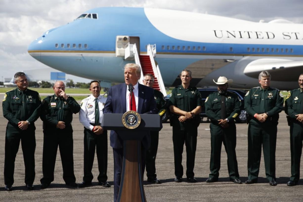 With Air Force One in the background, President Donald Trump speaks during a campaign event with Florida Sheriffs in Tampa, Fla., Friday, July 31, 2020.