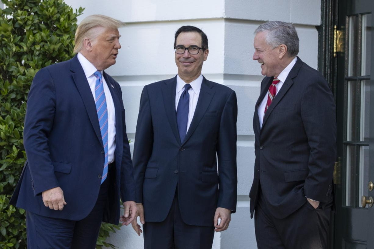 President Donald Trump, Treasury Secretary Steven Mnuchin, White House Chief of Staff Mark Meadows talk before Trump speaks with reporters on the South Lawn of the White House, Wednesday, July 29, 2020, in Washington. Trump is en route to Texas.