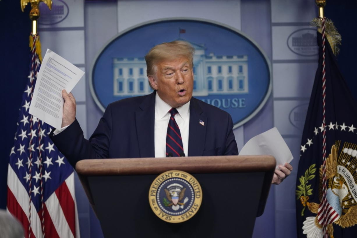 President Donald Trump holds articles as he speaks during a news conference at the White House on Thursday in Washington.