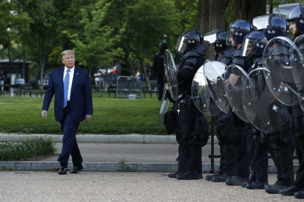 FILE - In this June 1, 2020, file photo President Donald Trump walks past police in Lafayette Park after visiting outside St. John's Church across from the White House in Washington.  When it comes to squelching protests in Democrat-run cities, Trump is eager to send in federal troops and agents -- even when local leaders are begging him to butt out.