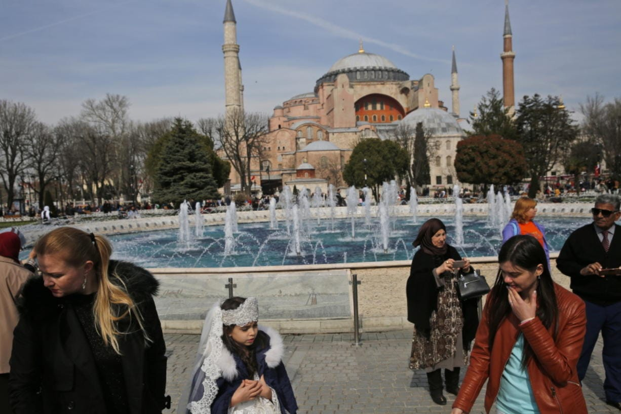 People walk in 2017 backdropped by the Byzantine-era Hagia Sophia, one of Istanbul's main tourist attractions, in the historic Sultanahmet district of Istanbul. The 6th-century building is now at the center of a heated debate between conservative groups who want it to be reconverted into a mosque and those who believe the World Heritage site should remain a museum.