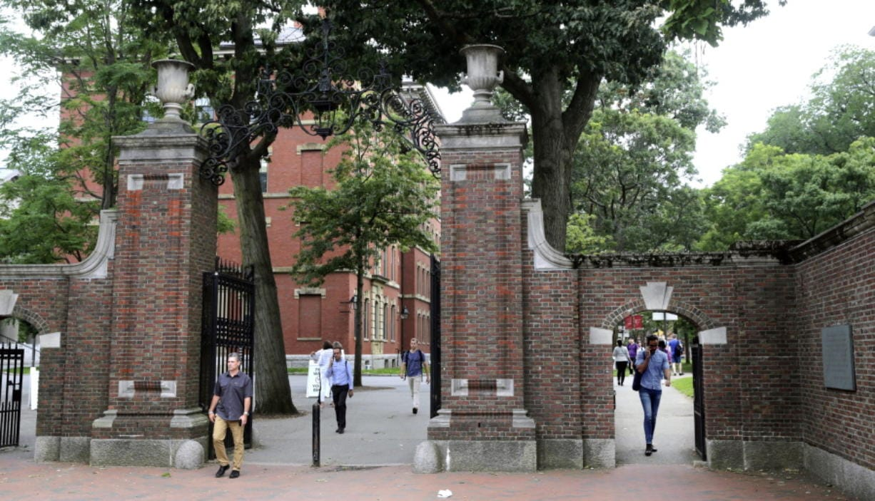 FILE - In this Aug. 13, 2019, file photo, pedestrians walk through the gates of Harvard Yard at Harvard University in Cambridge, Mass. Harvard and the Massachusetts Institute of Technology filed a federal lawsuit Wednesday, July 8, 2020, challenging the Trump administration's decision to bar international students from staying in the U.S. if they take classes entirely online this fall. Some institutions, including Harvard, have announced that all instruction will be offered remotely in the fall during the ongoing coronavirus pandemic.