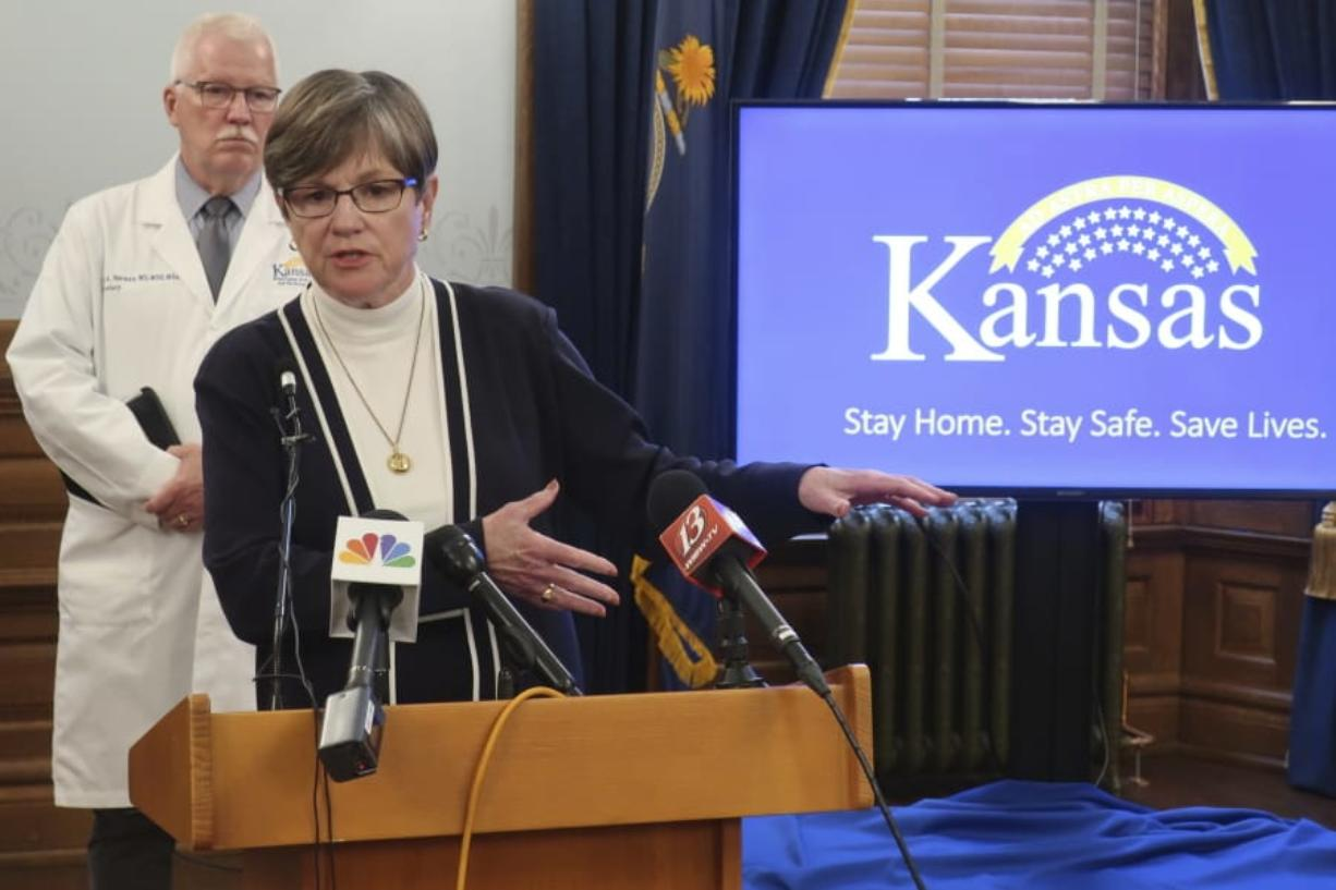 """Kansas Gov. Laura Kelly answers questions about the state's response to the coronavirus pandemic as Dr. Lee Norman, her health secretary, watches behind her, Monday, June 8, 2020, at the Statehouse in Topeka, Kan. Kelly the state's counties """"shouldn't feel pressure"""" to lift restrictions further if they're not seeing new cases and new hospitalizations decline."""
