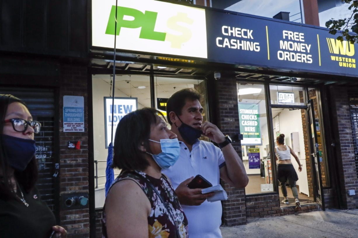 Magnolia Ortega, center, stands outside a Western Union with her husband Arturo Morales and their daughter Marlene after wiring money to her family in Mexico, Wednesday, June 24, 2020, in Staten Island, New York. Ortega lost her job cleaning houses amid the COVID-19 pandemic, reducing the monthly amount she sends home. She's considering returning to her hometown of San Jeronimo Xayacatlan but says there's no work there either and that would mean one less family member sending back one less monthly check.