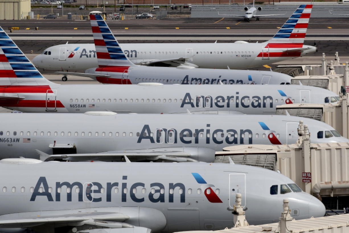 FILE - In this Wednesday, March 25, 2020, file photo, American Airlines jets sit idly at their gates as a jet arrives at Sky Harbor International Airport in Phoenix. American Airlines and four smaller carriers have reached agreement with the government for billions more in federal loans, a sign of the industry's desperate fight to survive a downturn in air travel caused by the virus pandemic. The Treasury Department said Thursday, July 2, 2020, that it had finalized terms of new loans to American, Spirit Airlines, Frontier Airlines, Hawaiian Airlines and SkyWest Airlines.