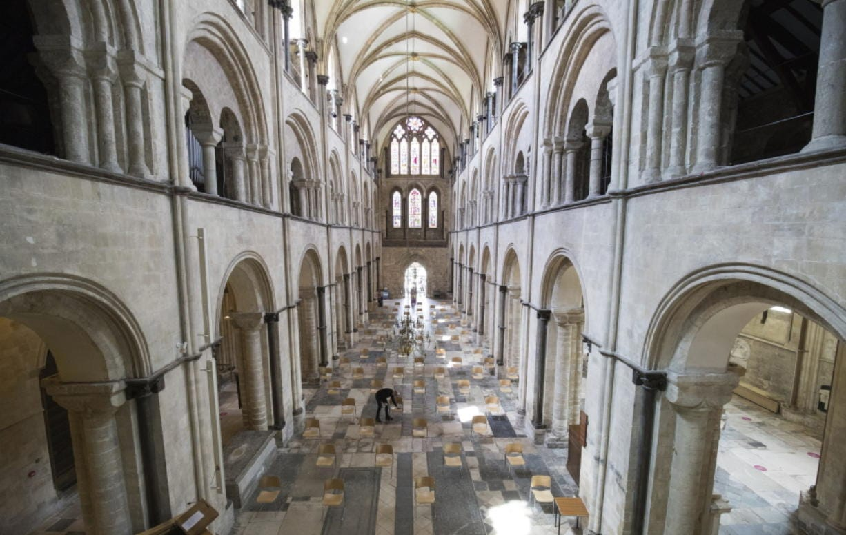 Senior Verger Luke Marshall cleans chairs that have be positioned to allow for social distancing, at Chichester Cathedral as they prepare to reopen for public worship on July 5, as further coronavirus lockdown restrictions are lifted in England, in Chichester, England,  Thursday July 2, 2020.